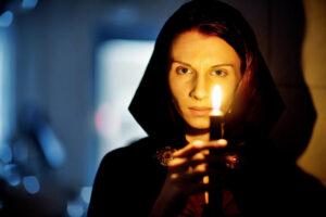 čarodějka v kápi se svící